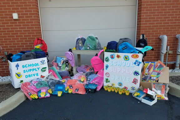 Photo of school supplies and multicolored backpacks raised during backpack campaign.