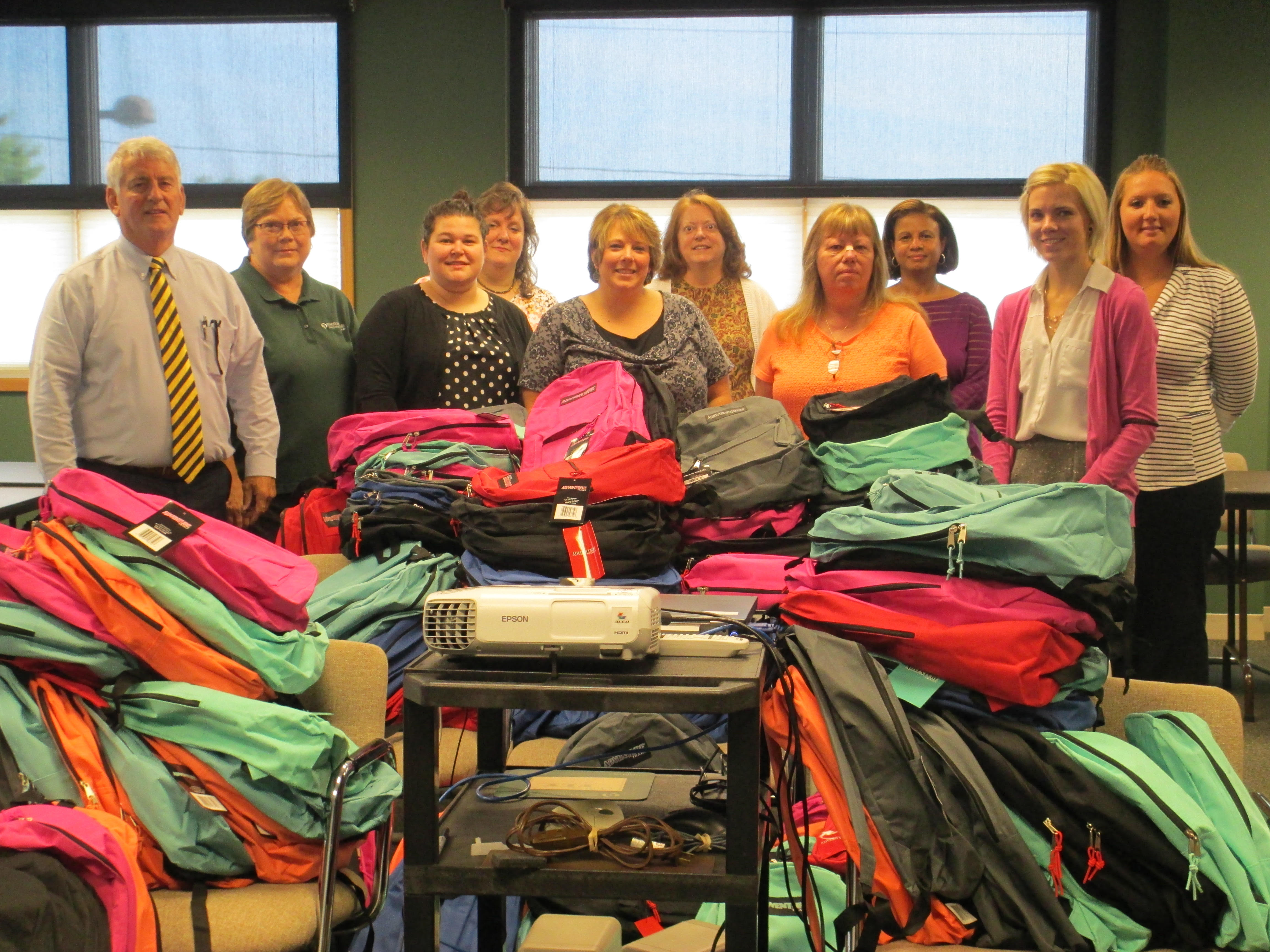 Photo of staff next to stacks of backpacks they just finished stuffing with school supplies.